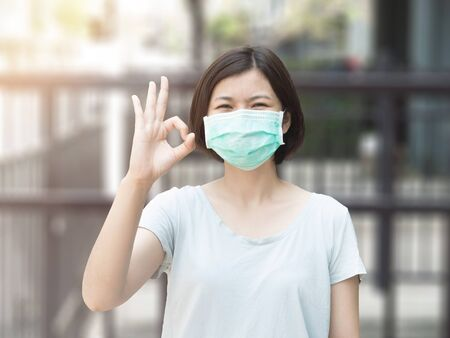 Asian woman wearing mask and ok finger hands gesture on blurred background with sunlight Reklamní fotografie