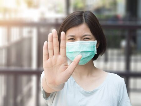 Asian woman wearing mask and stop finger hands gesture on blurred background with sunlight Reklamní fotografie