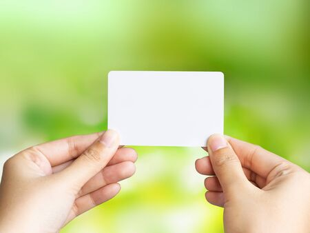 Woman holding blank business card on blurred green bokeh background