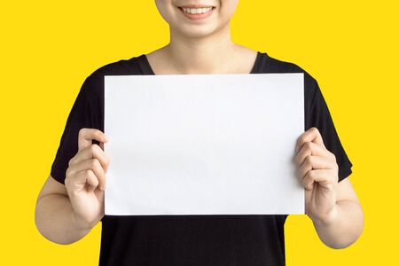 women holding blank paper isolated on yellow background Reklamní fotografie