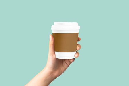 women hand holding mockup paper coffee cup on pastel green background