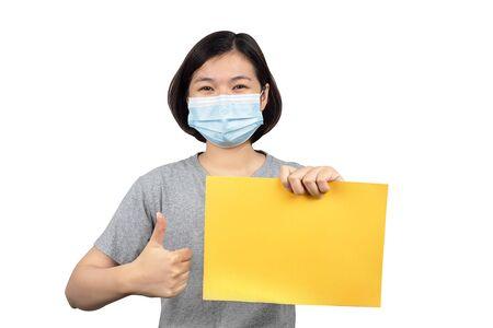asian women wearing protection medical masks to prevent corona virus and hand holding blank yellow paper isolated on white background Reklamní fotografie
