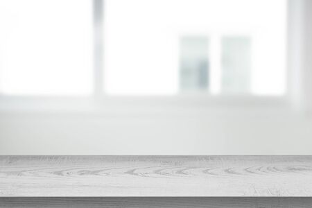 white wood table on abtract of blurred empty white room with window glass background