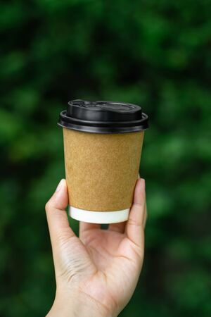 woman holding a paper coffee cup mockup on nature green blurred background.vertical image