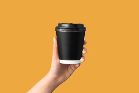 closeup of women hand holding paper coffee cup on yellow background Reklamní fotografie