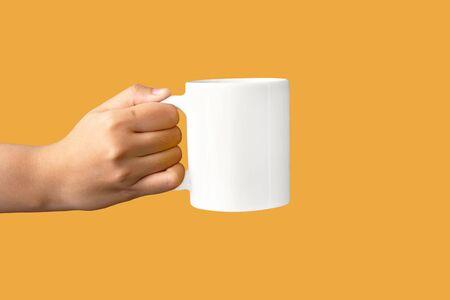 closeup of women hand holding white ceramic a mug mockup isolated on yellow