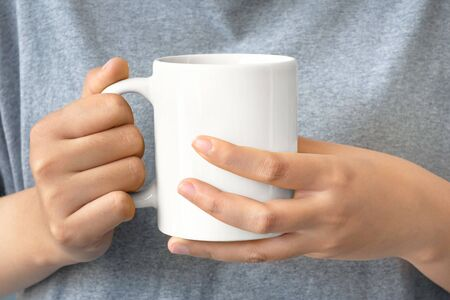 closeup of women hand holding white ceramic a mug mockup with clipping path Reklamní fotografie