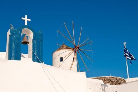 Church, windmill and greek flag in Oia, Santorini island of Greece