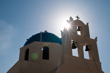 Greek church in Santorini island, Greece. Photo was taken against the sun to show the sun ray and flare