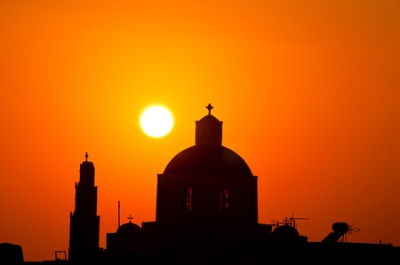 Church silhouette again the sunset in Santorini Stock Photo