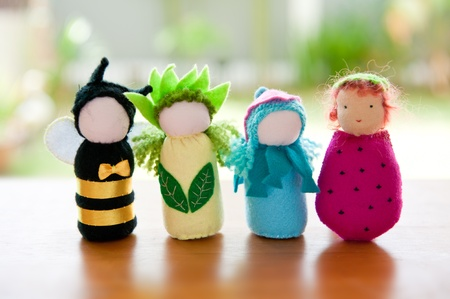 Handmade Waldorf soft toys on wooden table with garden in the background.