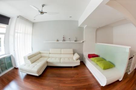 Soggiorno moderno con divano bianco, pavimento in legno e il trofeo di golf sul rack. Foto scattata con lente fisheye Archivio Fotografico