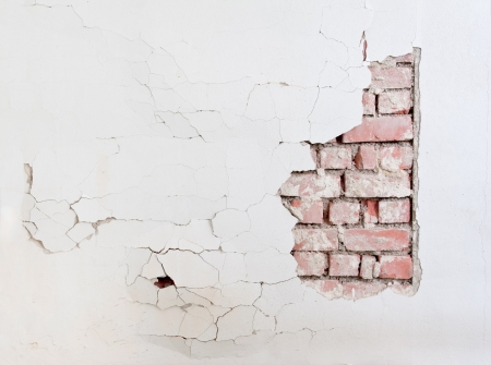 damaged cement: A damaged wall with crack and cement fall off