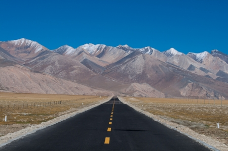 Long road ahead with mountain in front, Tibet, China.