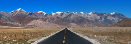 Panorama of landscape view of Tibet.Long & straight road ahead with high mountain range in front in the distance