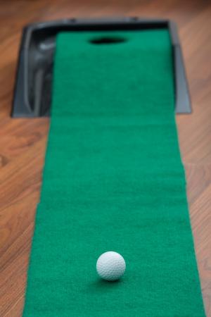 Golf ball on putting mat at home