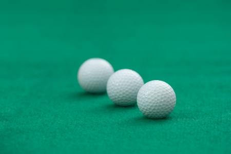 Three golf balls on green putting mat Stock Photo