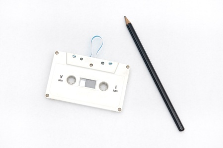 Use a pencil to unwind an audio cassette tape --- Old and obsolete technology Stock Photo