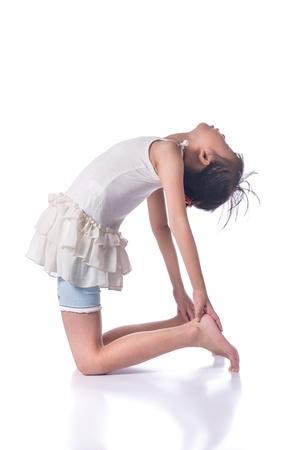 Little girl practicing yoga isolated on white background