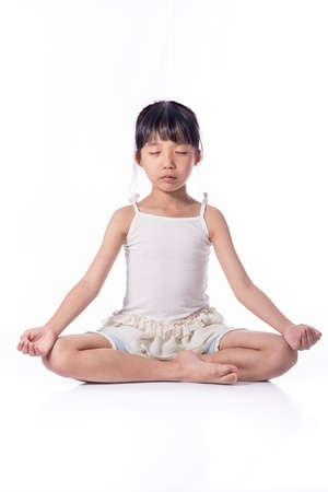 Little girl practicing yoga isolated on white background photo