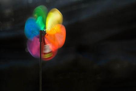 Colourful windmill rotating with strong wind against dark background
