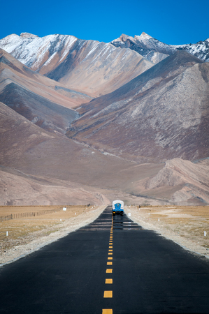A truck driving ahead on a straight road toward mountains