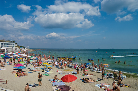 ODESSA, UKRAINE - August 15, 2015: Tourists sunbathe, swim and relax on beach having fun. Tourism is one of most important destinations in Europe. Hot summer. A good holiday season. Many tourists