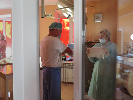 palpitations: Odessa, Ukraine - October 9th, 2014 :Operating unit. The team is preparing for the surgeon in the operating room. Due to the increasing incidence increasing worldwide demand for the services of a surgeon.