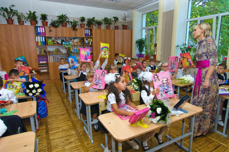Odessa, Ukraine - September 1, 2015: elementary school students at their desks with textbooks on the first day of the school year. Feast Day of Knowledge. Beginning of a new academic year. Editorial