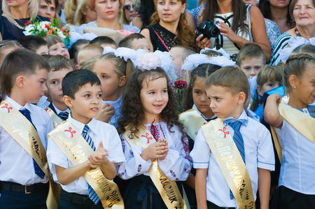 Odessa, Ukraine - September 1, 2015: elementary school students stand on the first day of the school year. Feast Day of Knowledge. Beginning of a new academic year.