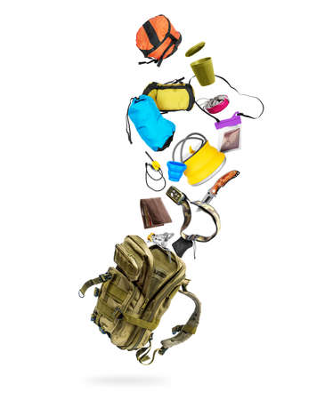 Various travel accessories flying out from military backpack, isolated on white background