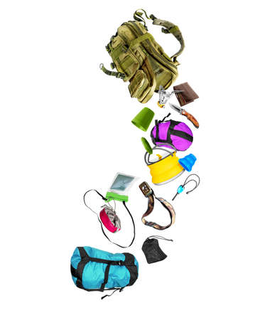 Various travel accessories falling from military backpack isolated on white background