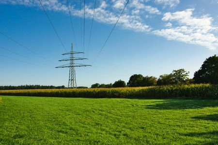 A high-voltage mast with transmission line, next to a railway line, behind a meadow and a corn field, in Upper Bavaria, south of Munich Stockfoto