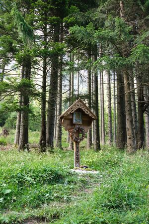 Catholic field cross made of wood, with Christ figure, at the edge of a forest in the Bavarian Alps