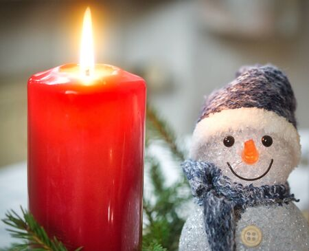 Candle lights up on the Advent wreath, next to it a small figure of a snowman