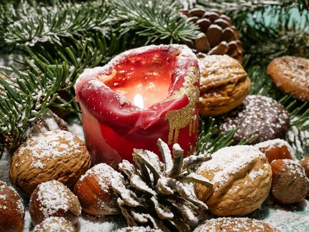 Christmas decoration, with green fir branches, red candle, various nuts, biscuits and small gingerbread cookies - focus on the candle, the background in blur