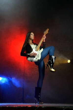 bass guitar women: Young beautiful woman playing the guitar on the scene Stock Photo