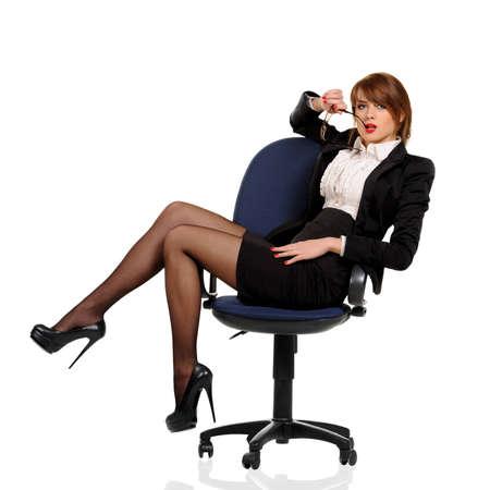 mujeres sentadas: Mujer de negocios joven sentado en la silla de oficina con el tel�fono celular en un fondo blanco Foto de archivo