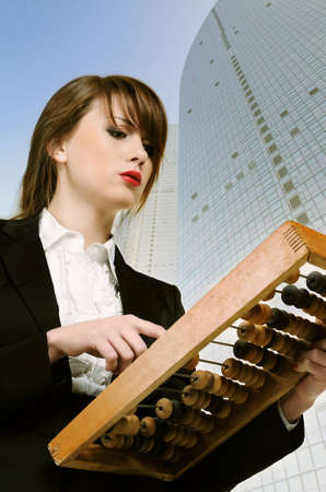 Young attractive businesswoman holding wooden abacus over city background  photo