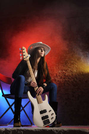 country girls: Young beautiful young singer is sitting on stage with a bass guitar