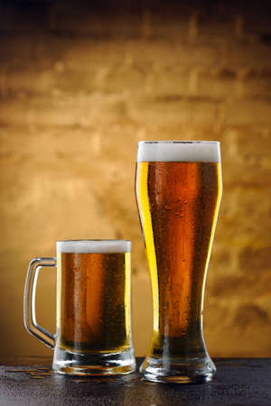 Two glasses of beer on the background of an old stone wall Stock Photo - 12867219