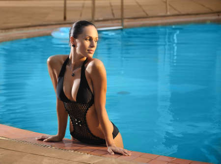 Young beautiful woman standing on the side of swimming pool photo