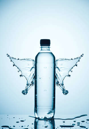 Plastic bottle and water splashes and drops on a blue background Stock Photo - 13101044