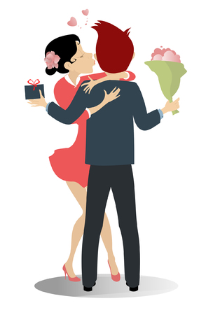 Kissing love couple isolated. Pretty young woman is kissing the boyfriend who holds a present and a bouquet of flowers