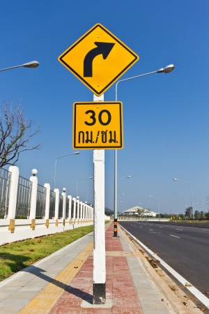 warns: Road Sign warns Drivers to Limit Speed Ahead Dangerous Curve. Stock Photo
