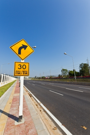 curvaceous: Road Sign warns Drivers to Limit Speed Ahead Dangerous Curve. Stock Photo