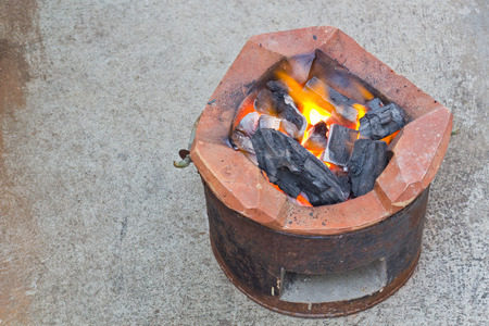 brazier: Charcoal brazier with cooking fire on cement ground. Stock Photo