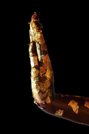 Buddha hand with gold leaf on black background photo