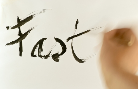 Writing word Fast, by bamboo brush with moving hand photo
