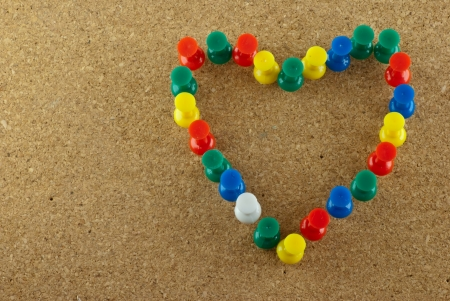 Colorful pins stick on corkboard in heart shape Stock Photo - 17160616